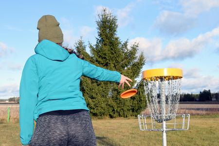Foto de Young woman throwing disc to target on disc golf course. - Imagen libre de derechos
