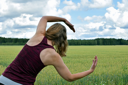 Photo pour Middle aged yoga woman stretching and exercise outdoors. Rear view, field on background. - image libre de droit