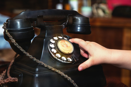 Photo for Child finger turning an old black vintage phone .Close up. - Royalty Free Image