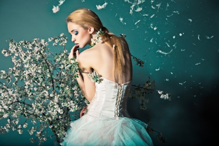 Photo pour Portrait of a woman in wedding dress behind the branches with flowers - image libre de droit