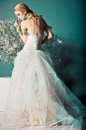 Photo pour Portrait of a woman in wedding dress behind the branches with flowers - image libre de droit