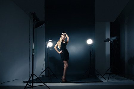 Photo pour Beautiful female model posing at studio in the light flashes - image libre de droit