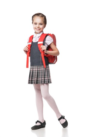 Photo pour Full height portrait of a smiling schoolgirl in uniform and with backpack standing on white background - image libre de droit