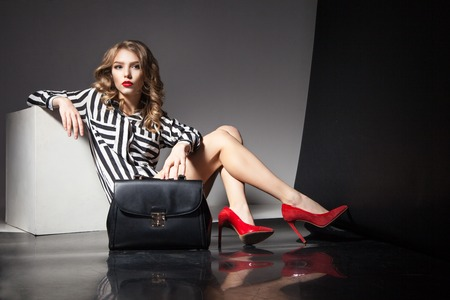 Photo pour Portrait of elegant beautiful blonde woman with red lips sitting near black fashion bag - image libre de droit