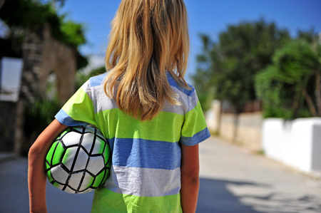 Photo for Long blond hair boy with football outdoors - Royalty Free Image