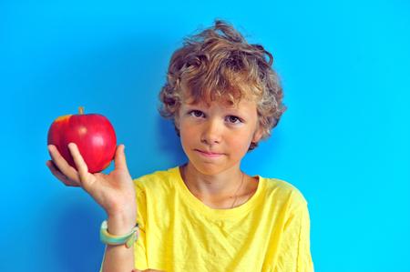 Foto de Shaggy boy with an apple at blue wall on background - Imagen libre de derechos