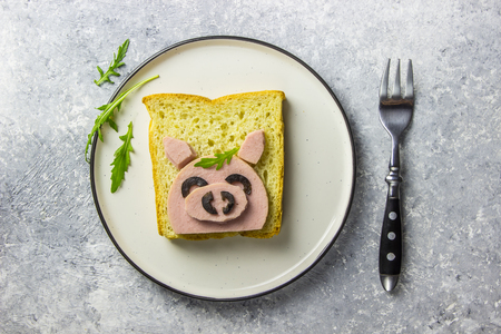 Photo pour Funny animal sandwich for kids shaped cute pig with boiled sausage and olives on white plate on grey - image libre de droit