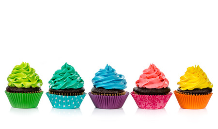 Foto de Chocolate cupcakes in a row with colorful icing on a white background. - Imagen libre de derechos