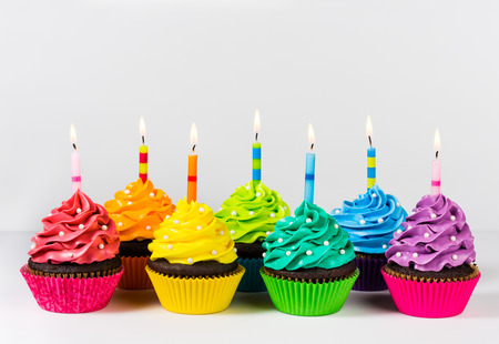 Photo pour Rows of colorful cup cakes decorated with birthday candles and sprinkles. - image libre de droit