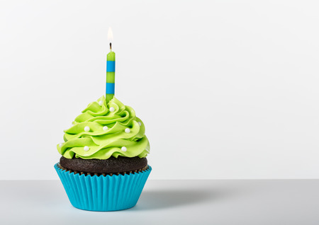 Photo for Chocolate Cupcake decorated with green icing, sprinkles and a lit birthday candle on a white background. - Royalty Free Image