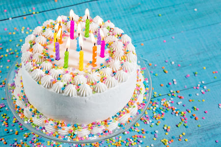 Foto de White Buttercream icing birthday cake with with colorful sprinkles and Candles over blue background - Imagen libre de derechos