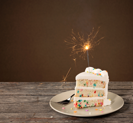 Photo pour Slice of Birthday Cake with colorful sprinkles and lit sparkler - image libre de droit