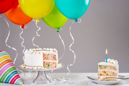 Photo pour White Buttercream birthday cake with colorful balloons and hat. - image libre de droit