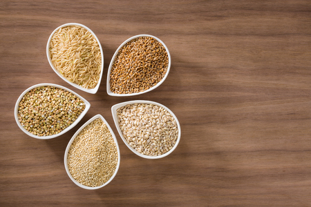 Photo pour An assortment of whole grains in bowls over a wooden background - image libre de droit