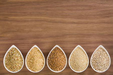 Photo for An assortment of whole grains in bowls over a wooden background - Royalty Free Image