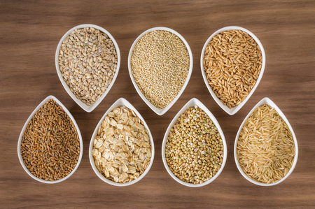 Foto de An assortment of whole grains in bowls over a wooden background - Imagen libre de derechos