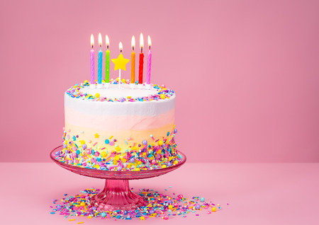 Photo pour Colorful Birthday cake with sprinkles over a pink background. - image libre de droit
