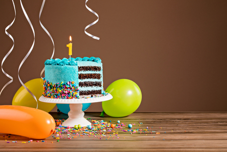 Photo pour Birthday cake with blue buttercream icing and colorful balloons and a number 1 candle. - image libre de droit