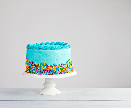 Photo pour Blue buttercream cake with colorful sprinkles over a light grey background. - image libre de droit