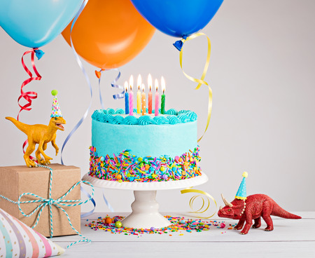 Photo pour Childs birthday party scene with blue cake, gift box, toy dinosaurs, hats and colorful balloons over light grey. - image libre de droit