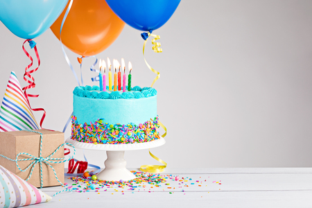 Photo pour Blue Birthday cake, presents, hats and colorful balloons over light grey. - image libre de droit