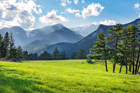 Foto de Idyllic summer landscape in Rocky Mountain National Park, colorado, with green mountain pastures and mountain range in the background. - Imagen libre de derechos