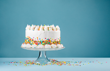 Photo pour White Birthday cake with colorful Sprinkles over a blue background. - image libre de droit