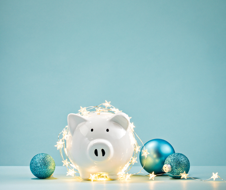 Photo pour White Piggy bank wrapped in a string of Christmas lights over a blue background. Saving concept. - image libre de droit