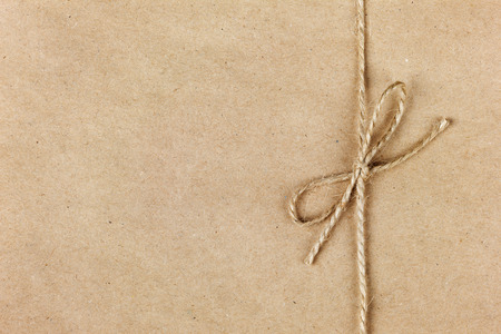 Photo pour string or twine tied in a bow on kraft paper background - image libre de droit