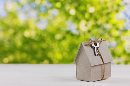 Foto de model of cardboard house with a bow of twine and key against green bokeh background. house building, loan, real estate or buying a new home concept. - Imagen libre de derechos