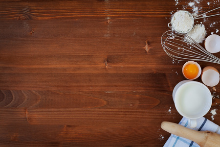Foto de Ingredients for baking dough including flour, eggs, milk, whisk and rolling pin on wooden rustic background, empty space for text, top view - Imagen libre de derechos