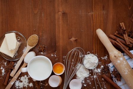 Photo pour Ingredients for baking dough including flour, eggs, milk, butter, sugar, cinnamon, anise star, whisk and rolling pin on wooden rustic background, empty space for text, top view - image libre de droit