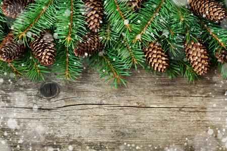 Foto de Christmas decoration of fir tree and conifer cone on textured wood background, magic snow effect, top view - Imagen libre de derechos