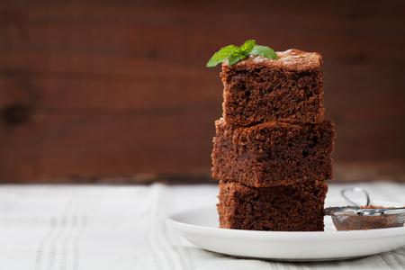 Foto de Brownie stack, closeup chocolate cake in plate on rustic wooden table - Imagen libre de derechos