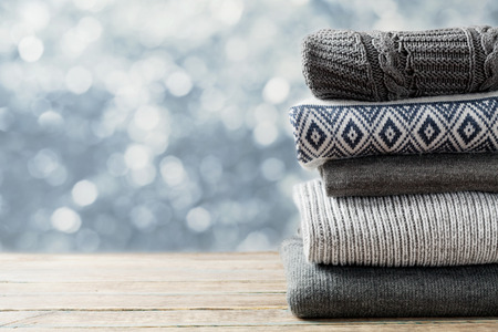 Foto de Pile of knitted winter clothes on wooden background, sweaters, knitwear, space for text - Imagen libre de derechos