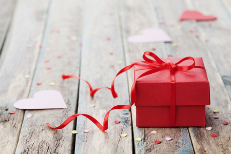 Foto de Gift box with red bow ribbon and paper heart on wooden table for Valentines day - Imagen libre de derechos