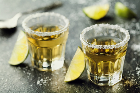 Photo for Tequila shot with lime and sea salt on black table - Royalty Free Image