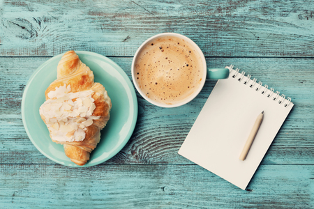 Foto de Coffee mug with croissant and empty notebook and pencil for business plan and design ideas on turquoise rustic table from above, cozy and tasty breakfast, vintage toned - Imagen libre de derechos