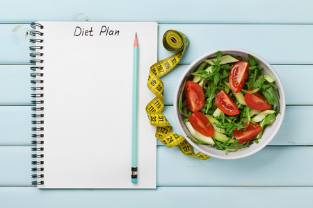 Foto per Diet plan, menu or program, tape measure and diet food of fresh salad on blue background, weight loss and detox concept, top view - Immagine Royalty Free