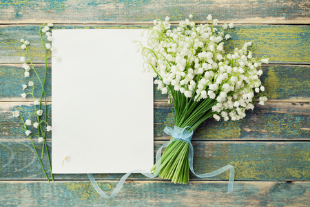 Photo pour Bouquet of flowers lily of the valley and empty paper sheet on rustic table from above, beautiful vintage card, top view, copy space for text, flat lay - image libre de droit