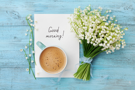 Foto de Coffee mug with bouquet of flowers lily of the valley and notes good morning on turquoise rustic table from above, beautiful breakfast, vintage card, top view, flat lay - Imagen libre de derechos