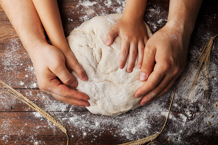 Foto de Father and child hands prepares the dough with flour, rolling pin and wheat ears on rustic wooden table from above. Homemade pastry for bread or pizza. Bakery background. - Imagen libre de derechos
