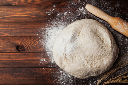 Foto de Dough with flour, rolling pin and wheat ears on rustic wooden table from above. Homemade pastry for bread or pizza. Bakery background. - Imagen libre de derechos