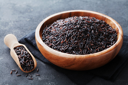 Photo pour Black rice in wooden bowl on a dark table - image libre de droit