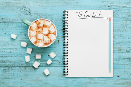 Photo for Cup of hot cocoa or chocolate with marshmallow and notebook with to do list on turquoise vintage table from above, christmas planning concept. Flat lay style. - Royalty Free Image