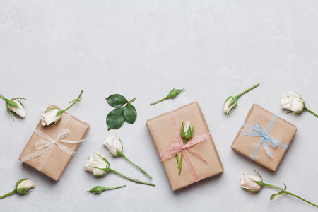 Photo pour Gift or present box wrapped in kraft paper and rose flower on gray table top view. Flat lay styling. Copy space for text. - image libre de droit