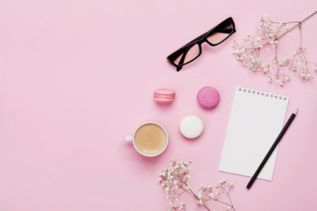 Photo pour Coffee, cake macaron, clean notebook, eyeglasses and flower on pink table from above. Female working desk. Cozy breakfast. Flat lay style. - image libre de droit