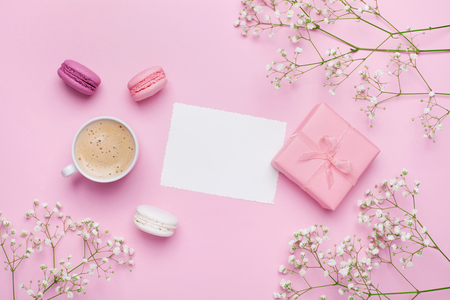 Foto de Morning cup of coffee, cake macaron, gift or present box and flower on pink table from above. Beautiful breakfast. Flat lay style. - Imagen libre de derechos