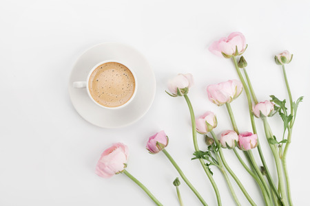 Photo for Beautiful spring Ranunculus flowers and cup of coffee on white desk from above. Greeting card. Breakfast. Pastel color. Clean space for text. Flat lay style. - Royalty Free Image