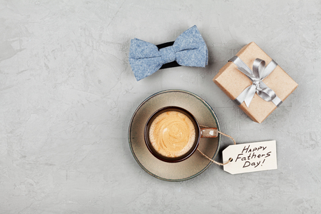 Photo for Morning cup of coffee, gift and bowtie on stone table top view in flat lay style for breakfast on Happy Fathers Day. - Royalty Free Image